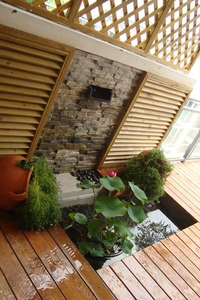 露台小花园用防腐木铺设,配有小水景,里有小金鱼和荷花哦